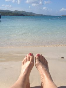Feet in the sand with ocean behind.