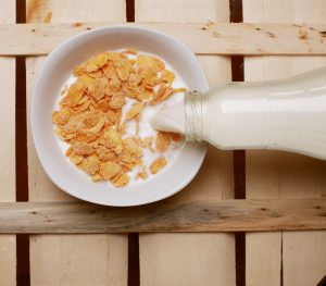 Cereal with milk poured from glass bottle.