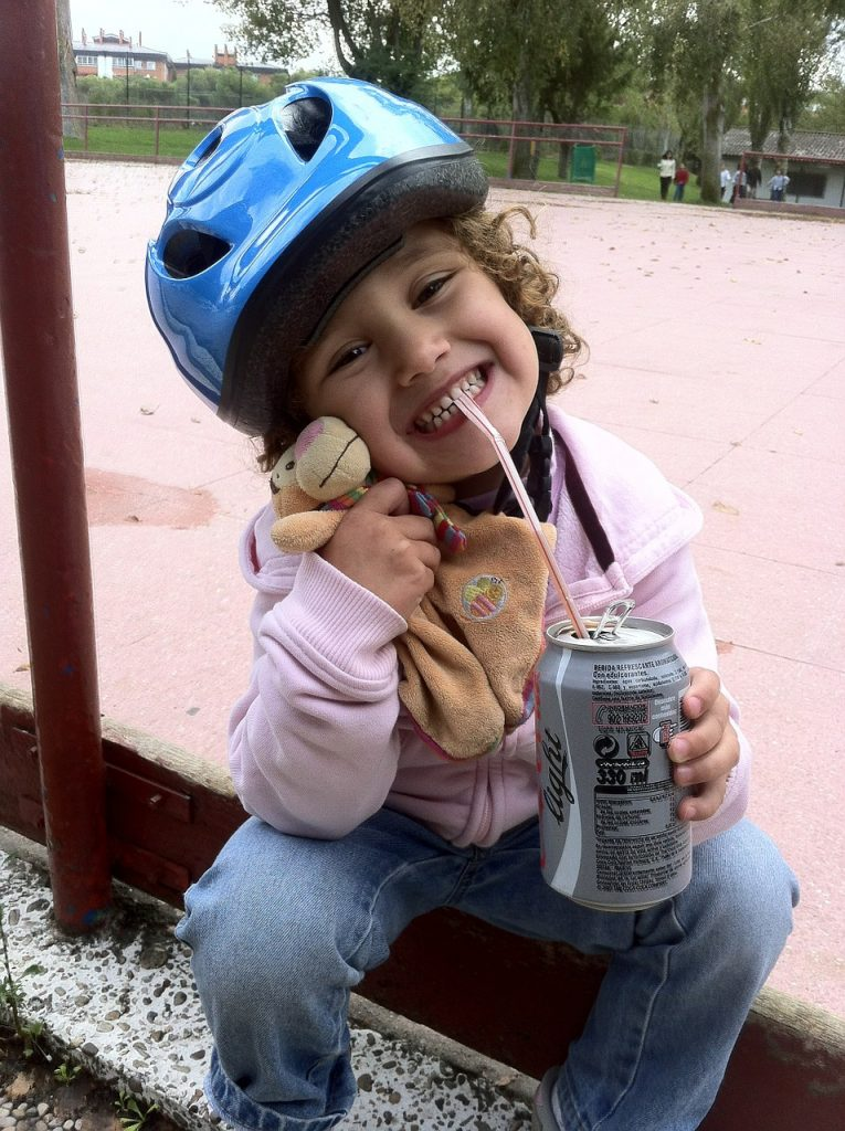 girl drinking cola. find out the caffeine content