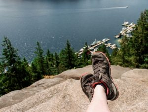 Hiking boots dangling over side of mountain with water view.