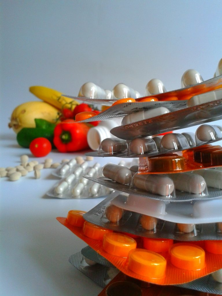 Stack of vitamins with veggies in background