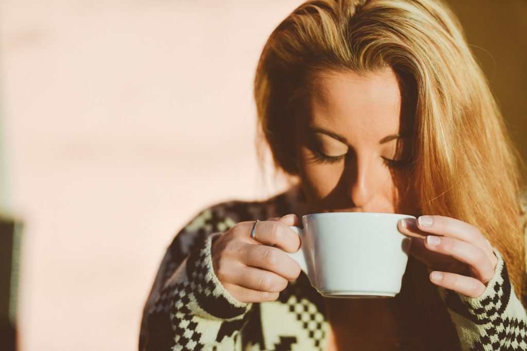 Blonde woman drinking beverage with caffeine