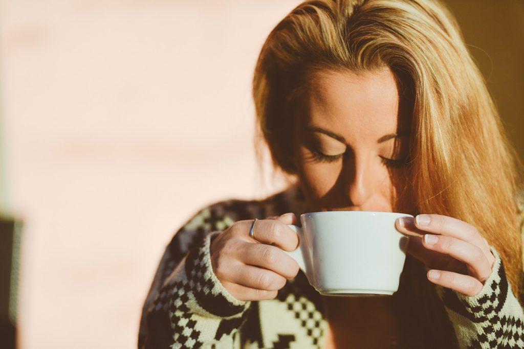 Blonde woman drinking beverage with caffeine