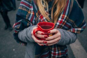 woman in plaid with coffee mug. find out caffeine content here.
