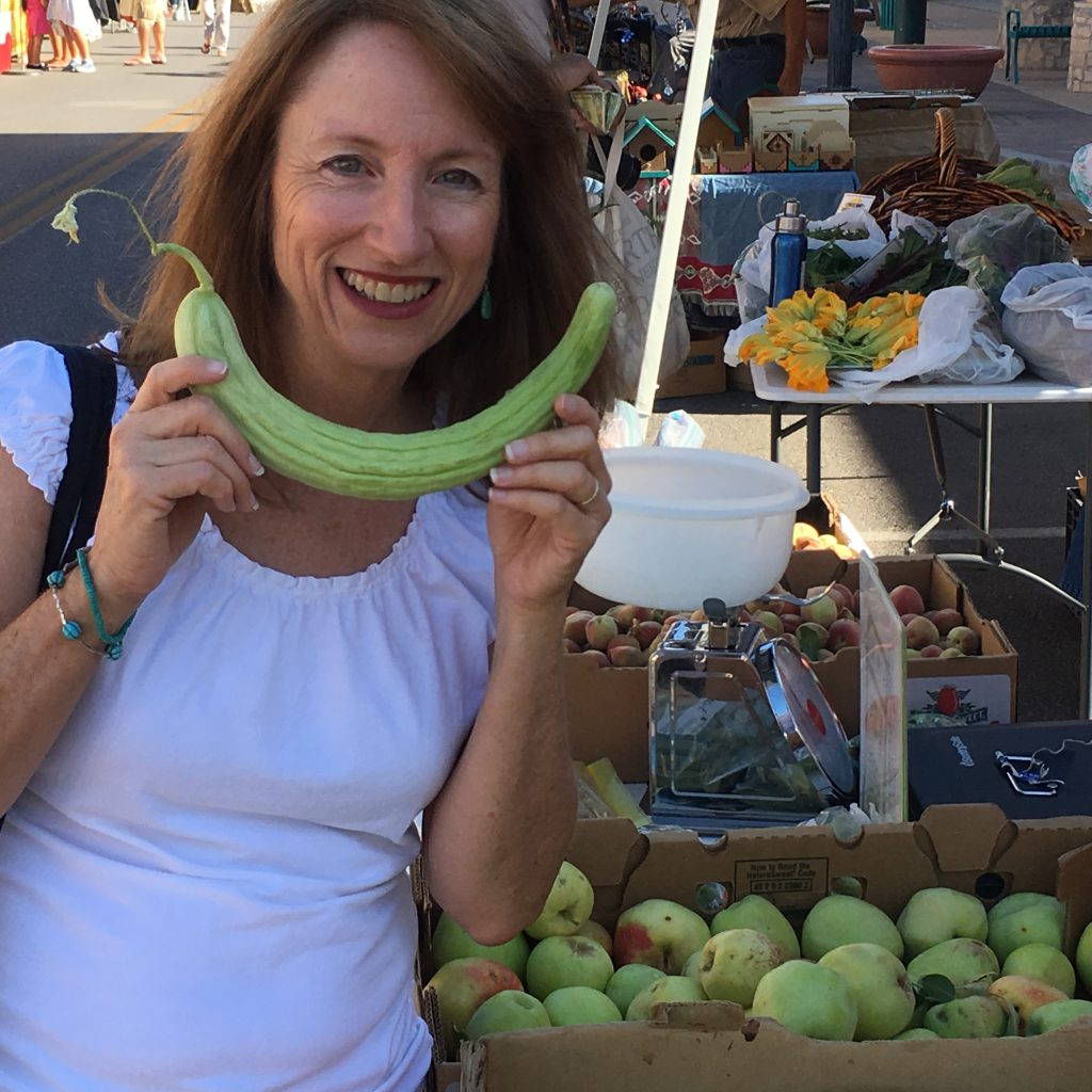 Bridget Swinney at the farmer's market with a cucumber. More at www.eatrightmama.com.