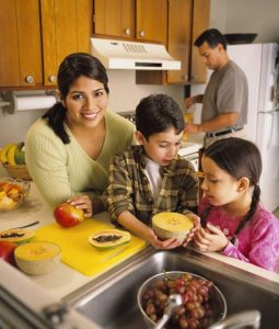 Hispanic family making fruit salad. Involve the kids in making lunch says Bridget Swinney at www.eatrightmama.com