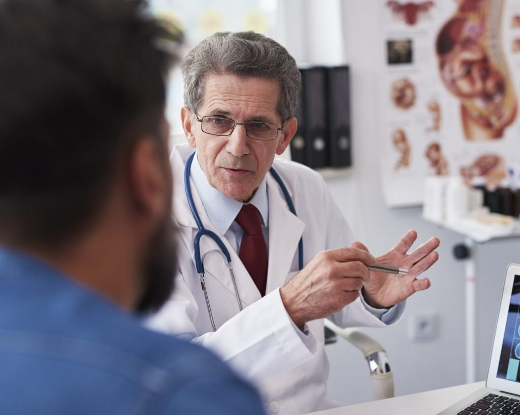 Senior doctor talking with his patient