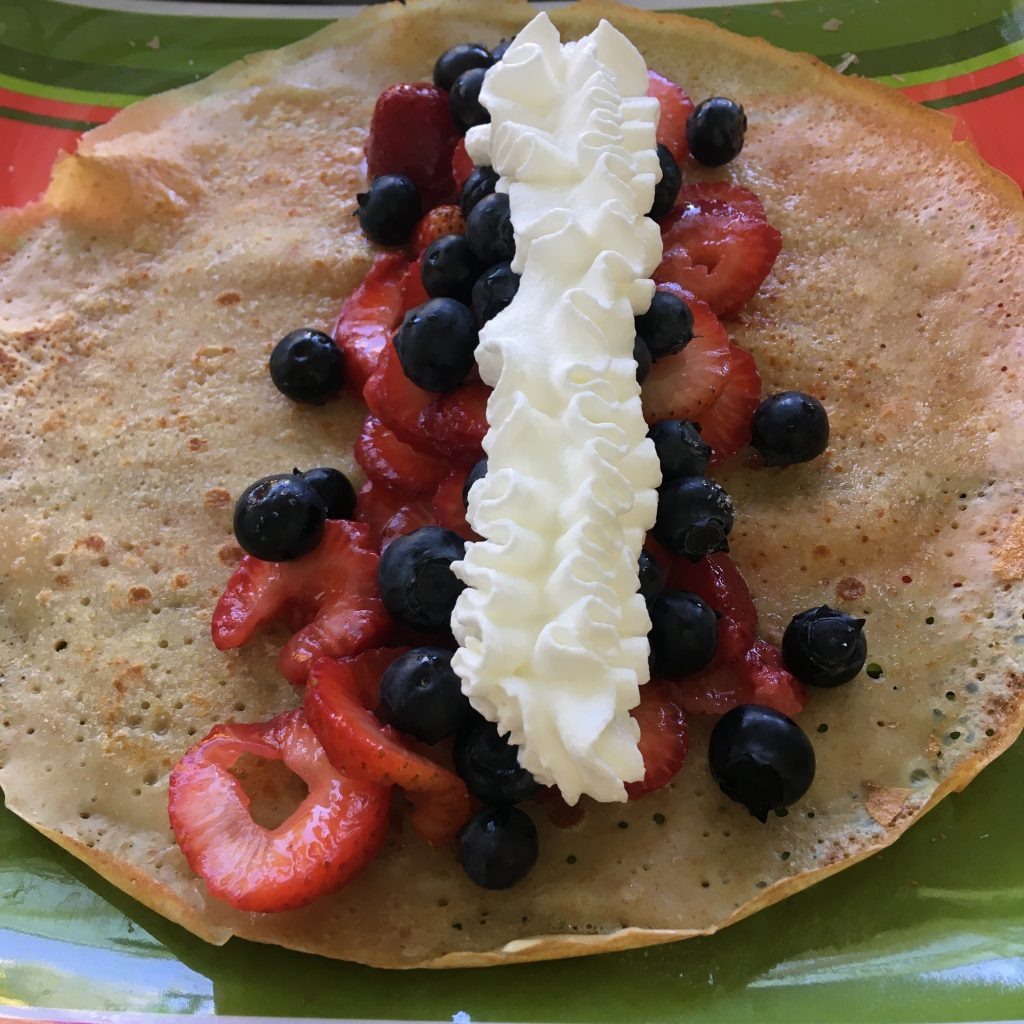 Crepe with strawberries blueberries and whipped cream