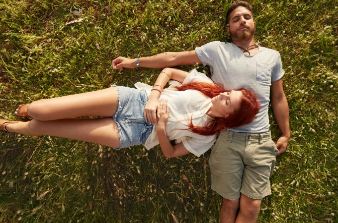 Young man and woman lying on the lawn sleeping. Overhead view of young couple resting together on the grass.